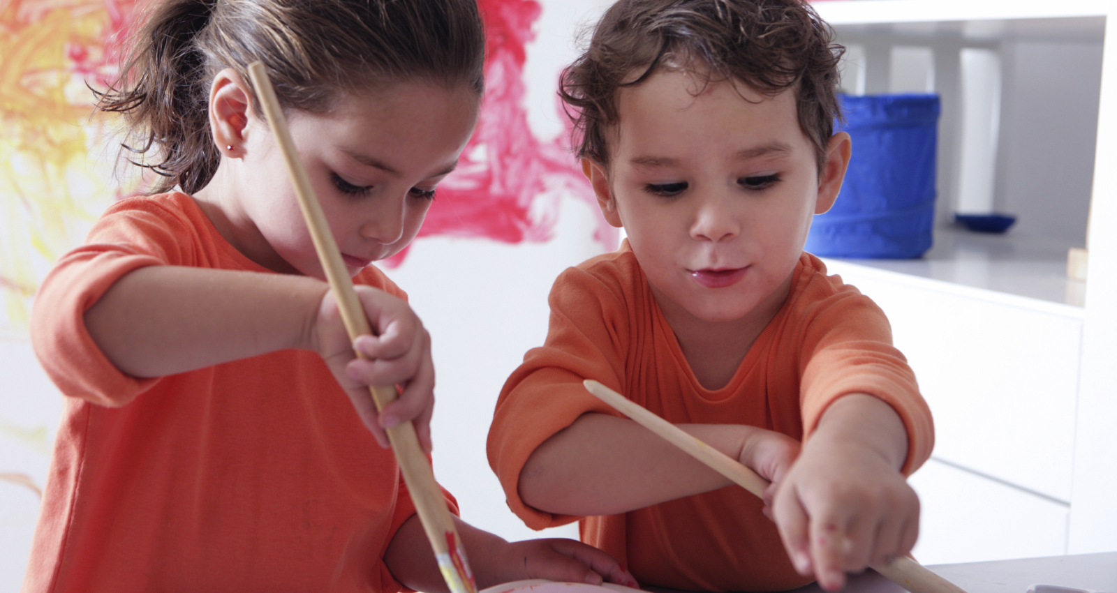 Two young children who are painting in a classroom