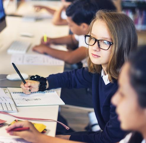 Une collégienne regarde l'écran d'ordinateur pendant un cours bilingue