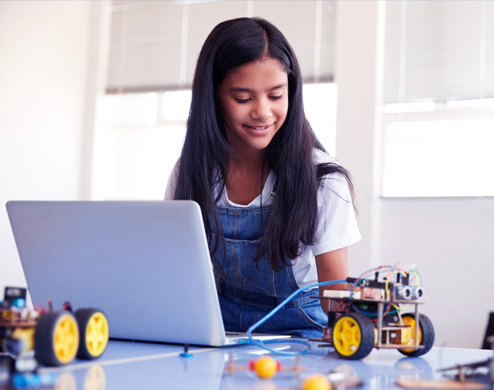 Middle school girl in technology using computers to create and code robots