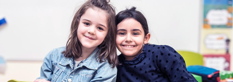 Deux étudiantes posent et sourient dans une classe de l'école bilingue de Paris