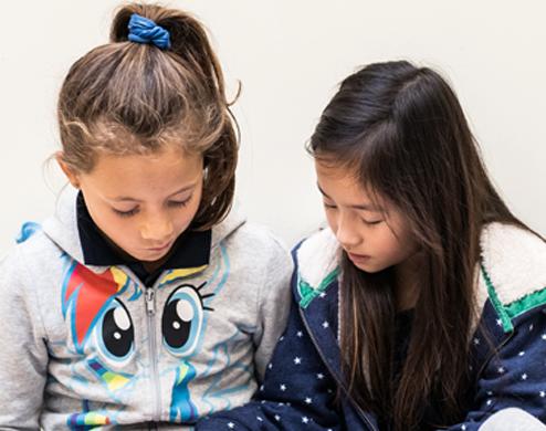 Deux jeunes filles sont en train de lire un livre bilingue
