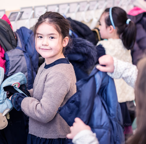 Young bilingual student taking off her coat