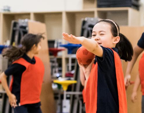 Une jeune étudiante est en train de lancer un ballon pendant un cours de sport
