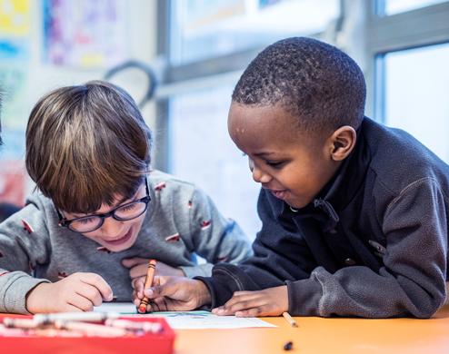 Deux garçons qui colorient pendant une activité à BISP